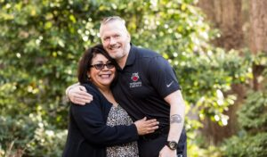 SEAC(R) John Wayne Troxell and Sandra Troxell embrace in their backyard after using their VA Home Loan.