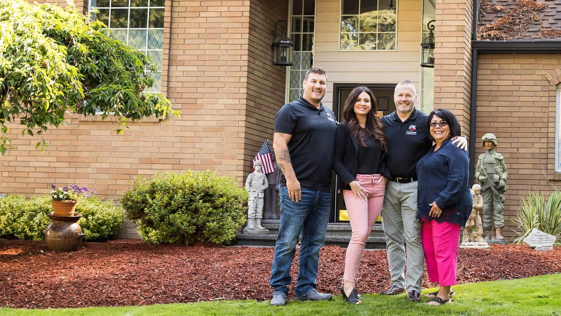 Mike Villano, Brooke Villano, SEAC(R) John Wayne Troxell and Sandra Troxell all stand smiling in front of the Troxell home after using the VA Home Loan.