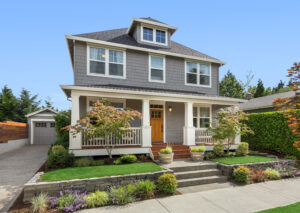 Beautiful craftsman home exterior on bright sunny day with green grass and blue sky